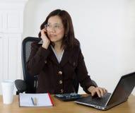 Rijpe bedrijfsvrouw die op celtelefoon communiceren terwijl op het werk Royalty-vrije Stock Afbeelding