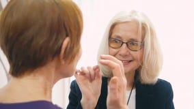 Rijpe bedrijfsvrouw in glazen die met dicht omhoog vriend spreken stock videobeelden