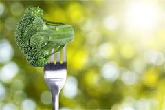Rijpe broccoli op vork over achtergrond stock afbeeldingen