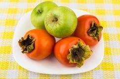 Rijpe dadelpruim en groene appelen in witte plaat Royalty-vrije Stock Foto's