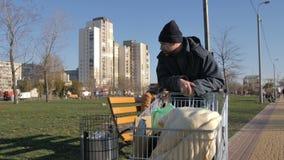 Rijpe dakloze mens die plastiek van afval verzamelen stock video