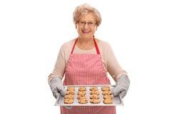 Rijpe dame die eigengemaakte koekjes houden stock afbeelding