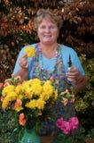 Rijpe dame werkende bloemen buiten portret royalty-vrije stock foto