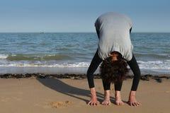 Rijpe de begroetingsyoga van de vrouwenzon op het strand Royalty-vrije Stock Afbeeldingen