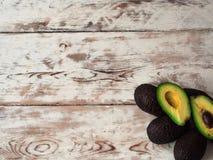 Rijpe die avocado in de helft op een houten lijst wordt gesneden, hoogste mening, exemplaarruimte Royalty-vrije Stock Foto