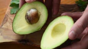 Rijpe die Avocado in Handen wordt gehalveerd stock videobeelden