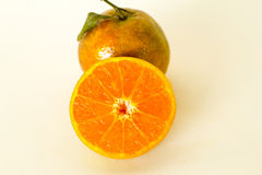 Rijpe die sinaasappelen op witte achtergrond worden geïsoleerd Sinaasappel in een besnoeiing Royalty-vrije Stock Afbeeldingen