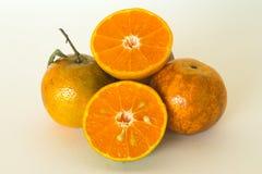Rijpe die sinaasappelen op witte achtergrond worden geïsoleerd Sinaasappel in een besnoeiing Stock Afbeelding