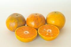 Rijpe die sinaasappelen op witte achtergrond worden geïsoleerd Sinaasappel in een besnoeiing Stock Foto's