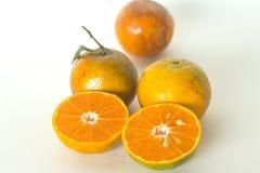 Rijpe die sinaasappelen op witte achtergrond worden geïsoleerd Sinaasappel in een besnoeiing Royalty-vrije Stock Foto's