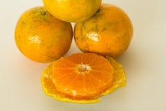 Rijpe die sinaasappelen op witte achtergrond worden geïsoleerd Sinaasappel in een besnoeiing Stock Fotografie