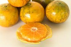 Rijpe die sinaasappelen op witte achtergrond worden geïsoleerd Sinaasappel in een besnoeiing Stock Afbeeldingen