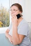 Rijpe die vrouw in gedachte na het spreken op de mobiele telefoon wordt verloren Royalty-vrije Stock Foto
