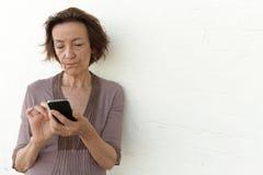Rijpe die vrouw met haar telefoon wordt geërgerd Stock Afbeelding