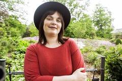 Rijpe donkerbruine vrouw in groene tuin die hoed, het glimlachen, het vriendschappelijke welkoming, het concept van levensstijlme Stock Foto