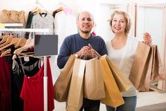 Rijpe echtgenoten die zakken met aankopen dragen stock foto's
