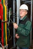 Rijpe elektricien die in bouwvakker met kabels werkt Royalty-vrije Stock Afbeeldingen