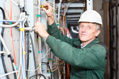 Rijpe elektricien die in bouwvakker met kabels werkt Stock Foto