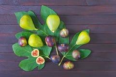 Rijpe fig.vruchten met groene bladeren van vijgeboom op donkere houten achtergrond Vlak leg stock foto