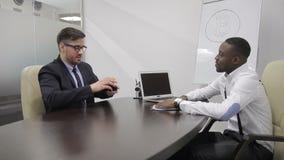 Rijpe financiële analitisch heeft een baangesprek met Afrikaanse werkgever van het opstarten van de bitcoininvestering stock video