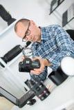 Rijpe fotograaf die camera met het overdrijven glas controleren Royalty-vrije Stock Fotografie