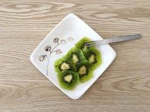 Rijpe Gesneden Kiwi op Moderne Witte Plaat met Lichte Eiken Houtachtergrond Royalty-vrije Stock Foto