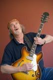 Rijpe gitarist die naar de hoge nota's zoekt stock foto's