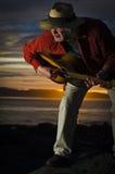 Rijpe gitarist die uit een riff busting bij zonsondergang royalty-vrije stock fotografie