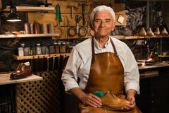 Rijpe glimlachende schoenmaker in de schoenen van de workshopholding Royalty-vrije Stock Foto