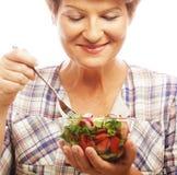 Rijpe glimlachende vrouw die salade eten Stock Afbeeldingen