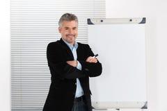 Rijpe glimlachende zakenman die presentatie op flipchart maken Stock Foto's