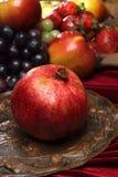 Rijpe granaatappel in druppeltjes van water op een oude schotel tegen een verticale achtergrond van vele vruchten, Royalty-vrije Stock Afbeeldingen