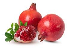 Rijpe granaatappelvruchten met bladeren op de witte achtergrond stock foto