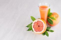 Rijpe grapefruits met halve plak, groen bladeren en sap op zachte witte houten raad Gezonde vruchten de zomerachtergrond Stock Fotografie