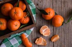 Rijpe heerlijke mandarines met schil op donkere houten lijst royalty-vrije stock afbeelding