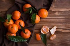 Rijpe heerlijke mandarines met schil op donkere houten lijst royalty-vrije stock fotografie