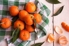 Rijpe heerlijke mandarines met schil op witte houten lijst stock foto's