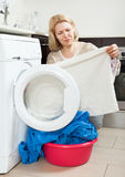 Rijpe huisvrouw die witte kleren cheking Royalty-vrije Stock Afbeeldingen