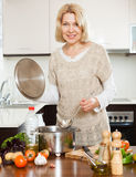 Rijpe huisvrouwen kokende soep Royalty-vrije Stock Afbeelding