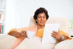 Rijpe Indische vrouw die computertablet gebruiken Royalty-vrije Stock Fotografie