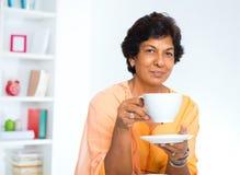 Rijpe Indische vrouw het drinken koffie Stock Afbeeldingen