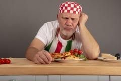 Rijpe Italiaanse Chef-kok die een maaltijd bekijken die hij voorbereidingen heeft getroffen stock foto