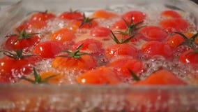 Rijpe kersentomaten die in een glaspan koken stock videobeelden