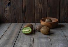 Rijpe kiwi op een houten achtergrond in een houten kom royalty-vrije stock afbeelding