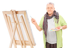 Rijpe kunstenaar die op een schildersezel trekken Stock Fotografie