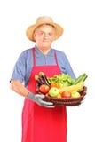 Rijpe landbouwersmens die een mand houdt Royalty-vrije Stock Foto