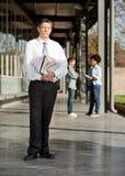 Rijpe Leraar With Books Standing op Universiteit Stock Afbeeldingen