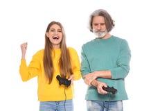 Rijpe man en jonge vrouw het spelen videospelletjes met geïsoleerde controlemechanismen stock foto