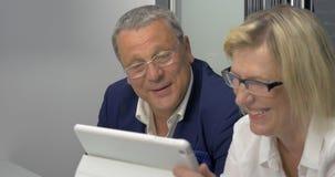 Rijpe man en vrouw die zaken met tabletpc doen stock videobeelden