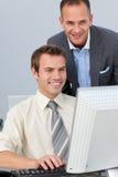 Rijpe manager die het werk van zijn werknemer controleert stock foto's